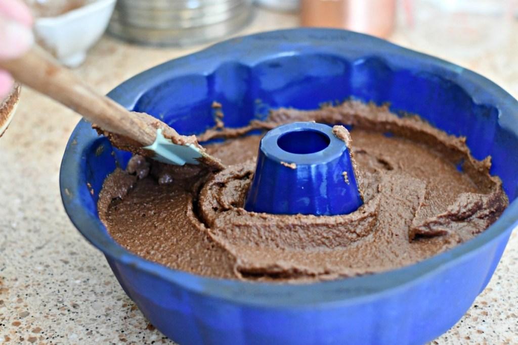 pouring keto chocolate cake into a bundt pan