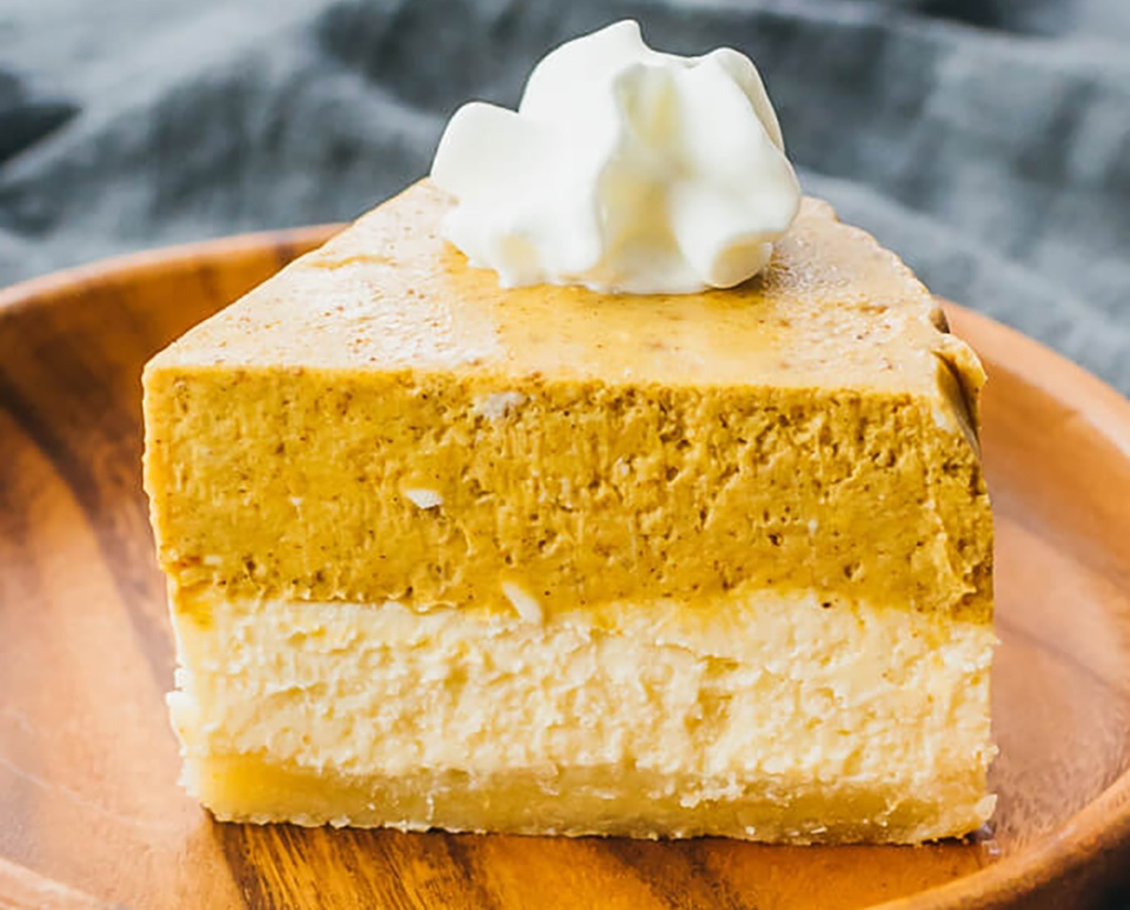 slice of pumpkin cheesecake with whipped cream from Savory Tooth