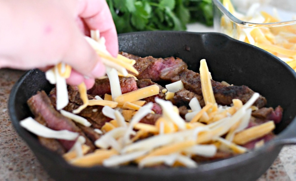 topping sliced steak with cheese for steak nachos