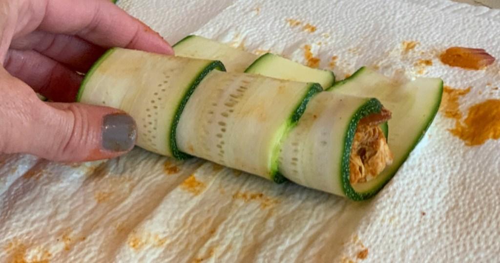 rolling up keto zucchini enchiladas