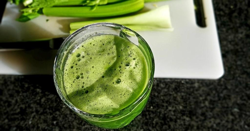 celery juice with celery on cutting board