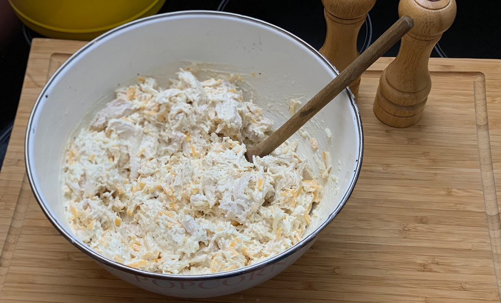 mixing shredded chicken and cheese in bowl