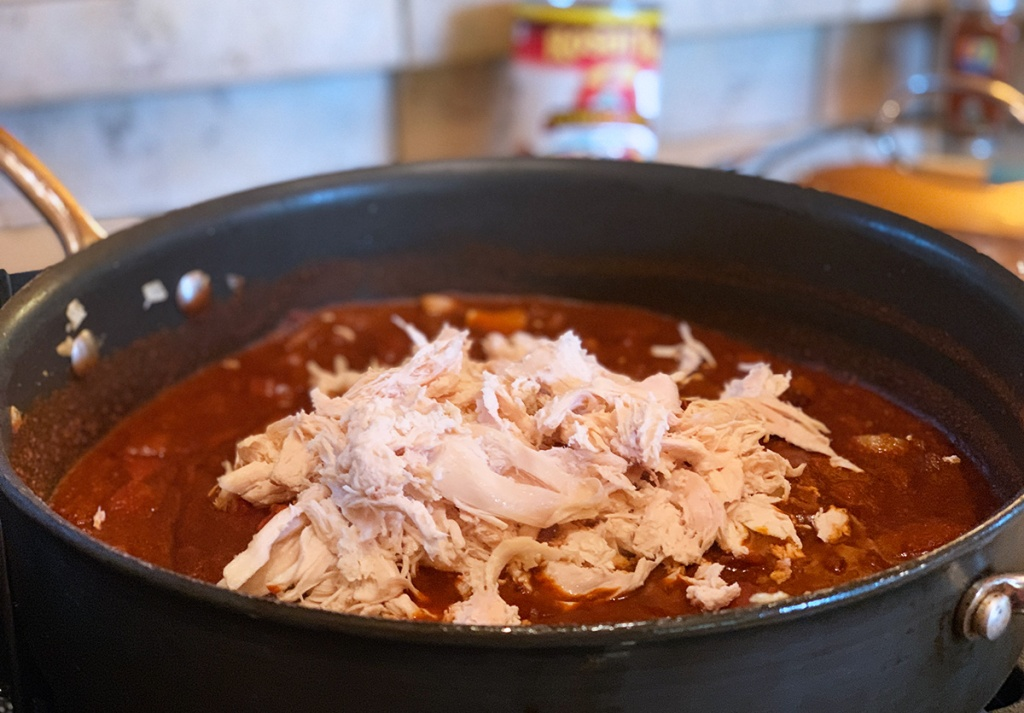 simmering chicken and enchilada sauce