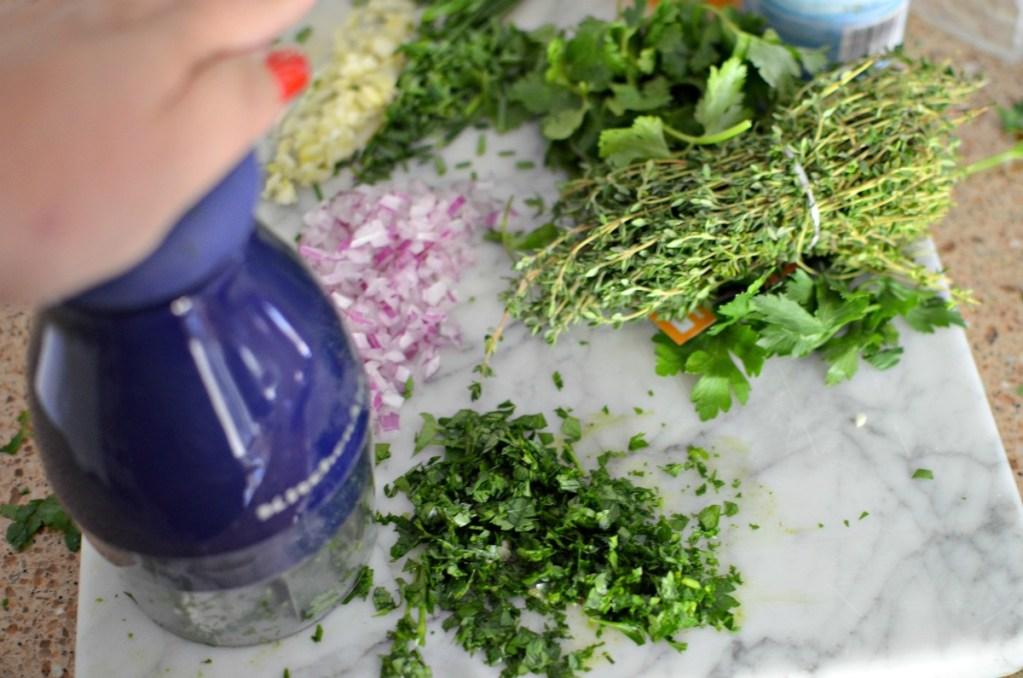 using hand chopper to make chimichurri sauce