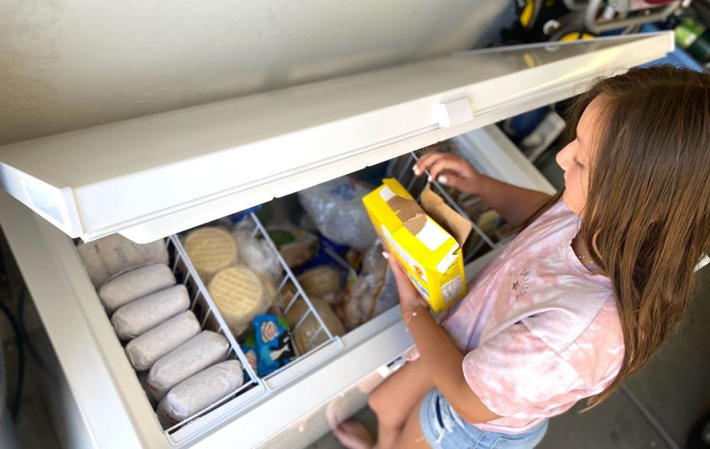 girl pulling food from deep freezer