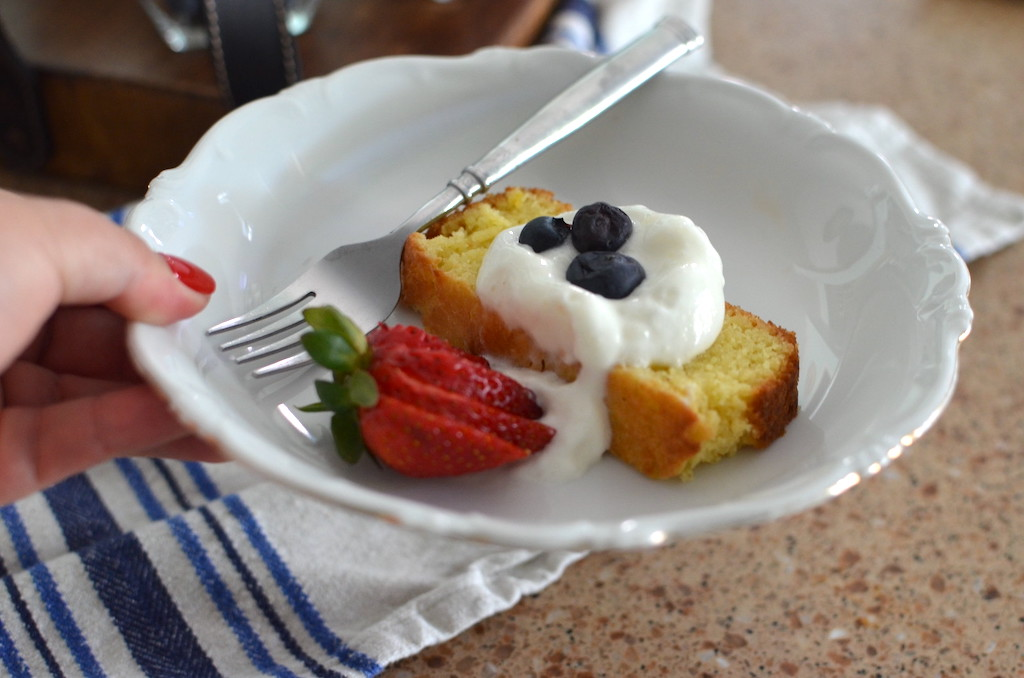 holding keto lemon pound cake on plate with fresh whipped cream & berries