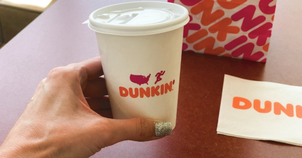hand holding hot coffee at Dunkin'