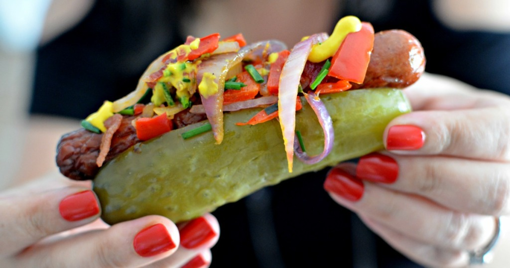 holding a pickle hot dog loaded with condiments