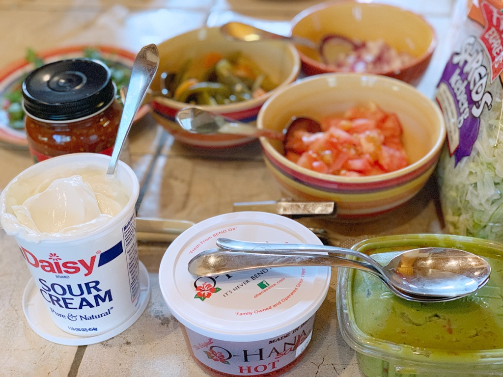 sour cream, guacamole, and other toppings for nacho bar