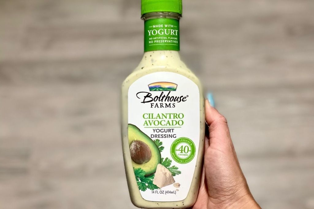 A hand holding a bottle of cilantro avocado salad dressing