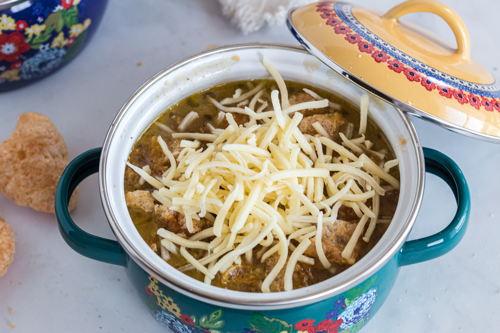 french onion soup with shredded cheese in dutch oven