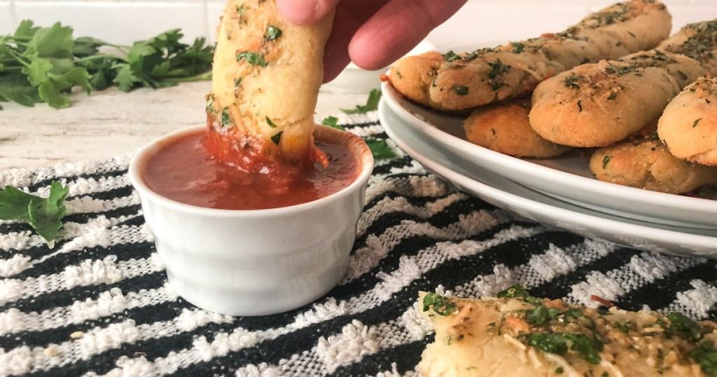 dipping breadstick in marinara sauce
