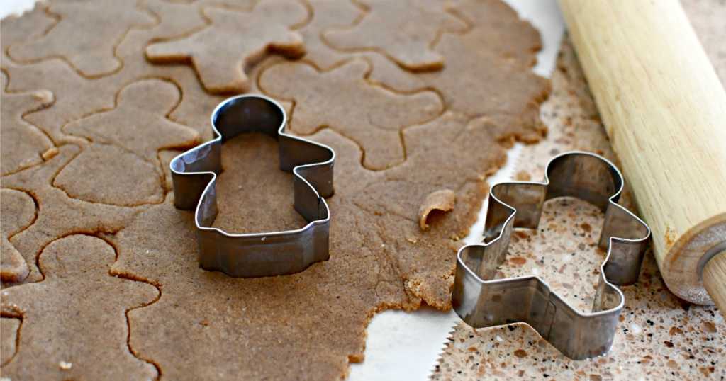 cutting out keto gingerbread cookies with cookie cutter