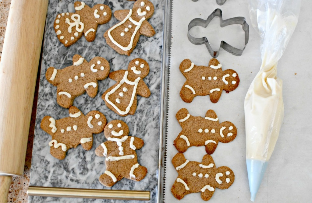piping frosting onto keto gingerbread cookies