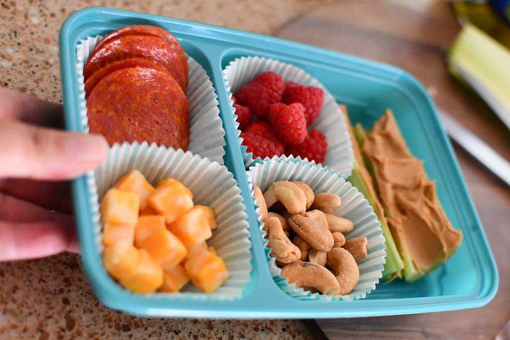bento-style keto lunch with pepperoni, cheese, berries, nuts