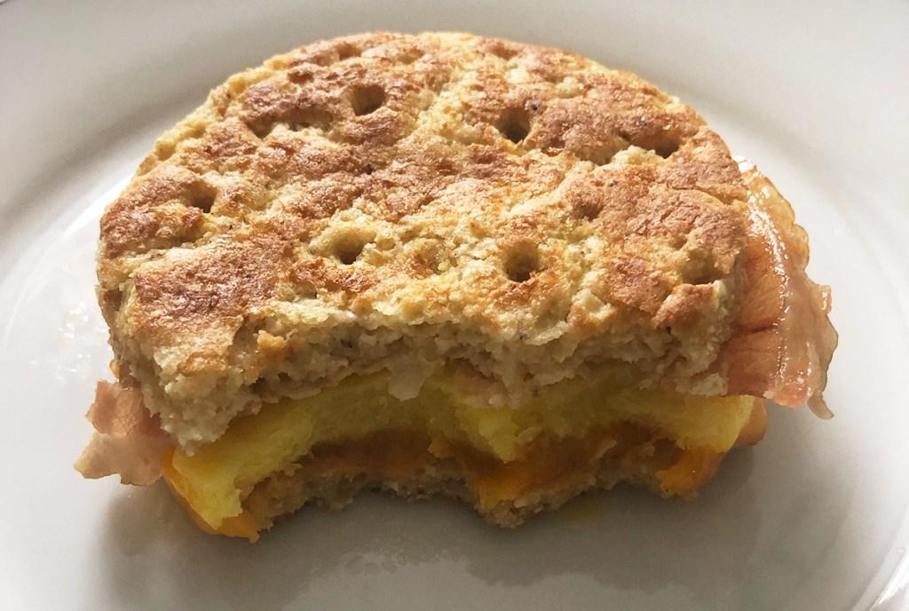 bite taken out of realgood foods cauliflower cheese bread breakfast sandwich