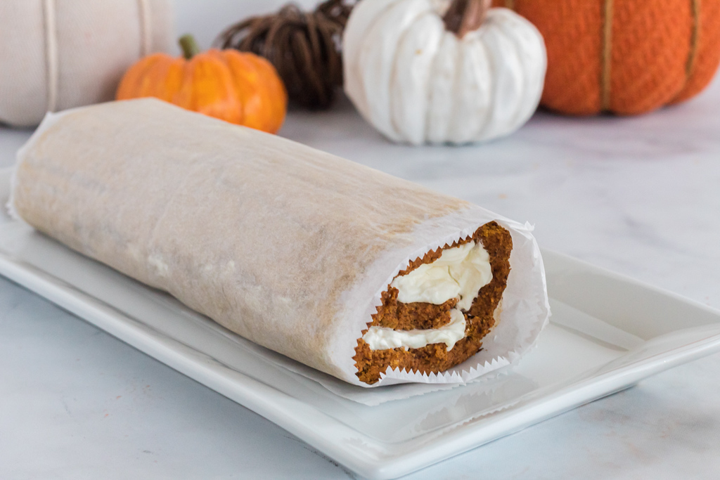 keto pumpkin roll rolled up and wrapped in parchment paper