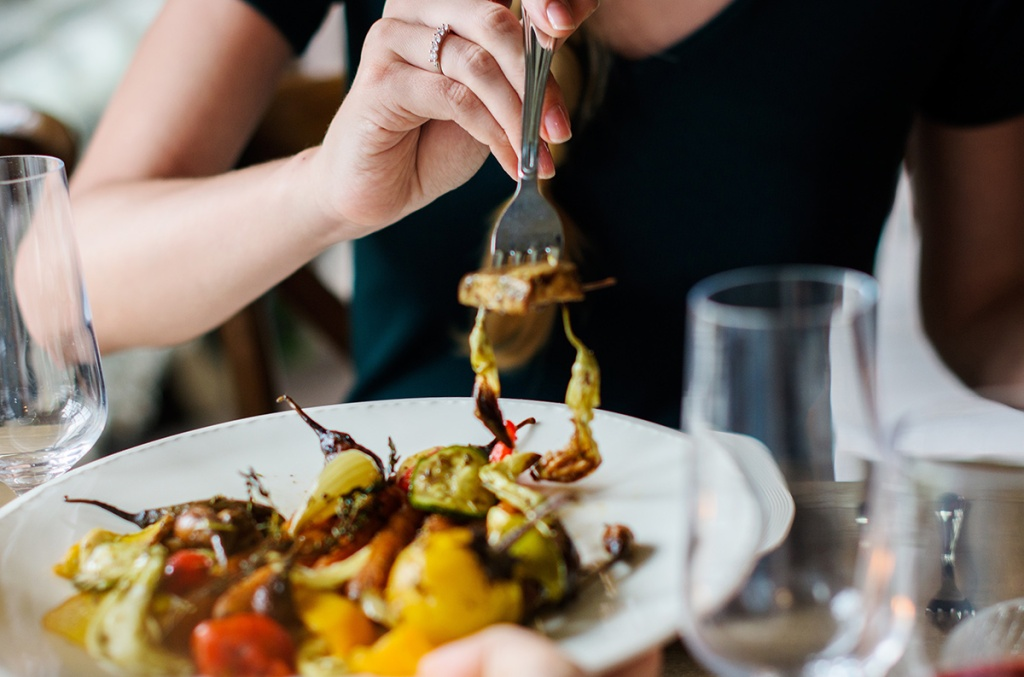 woman with fork of roasted vegetables
