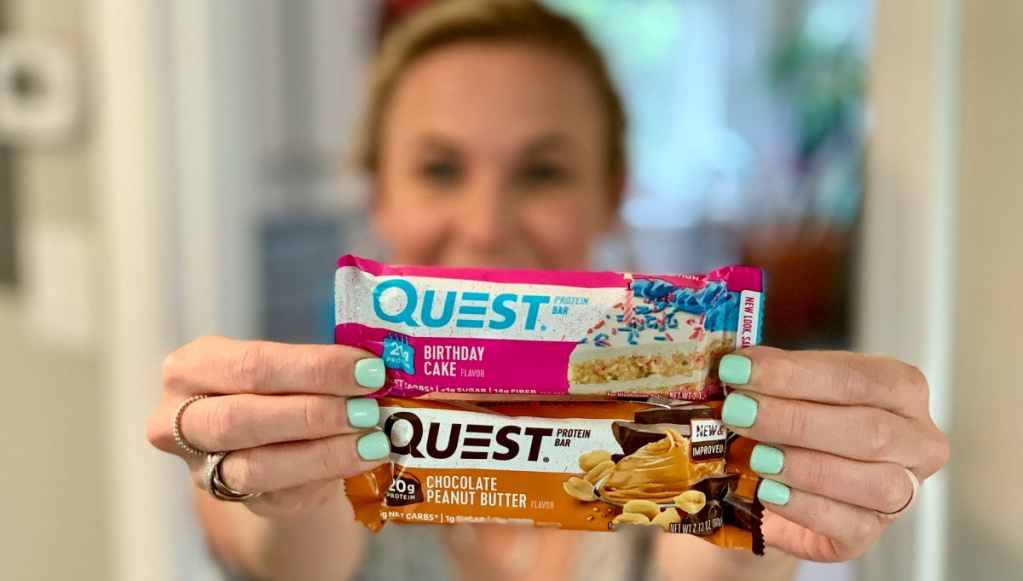 woman holding Quest protein bars