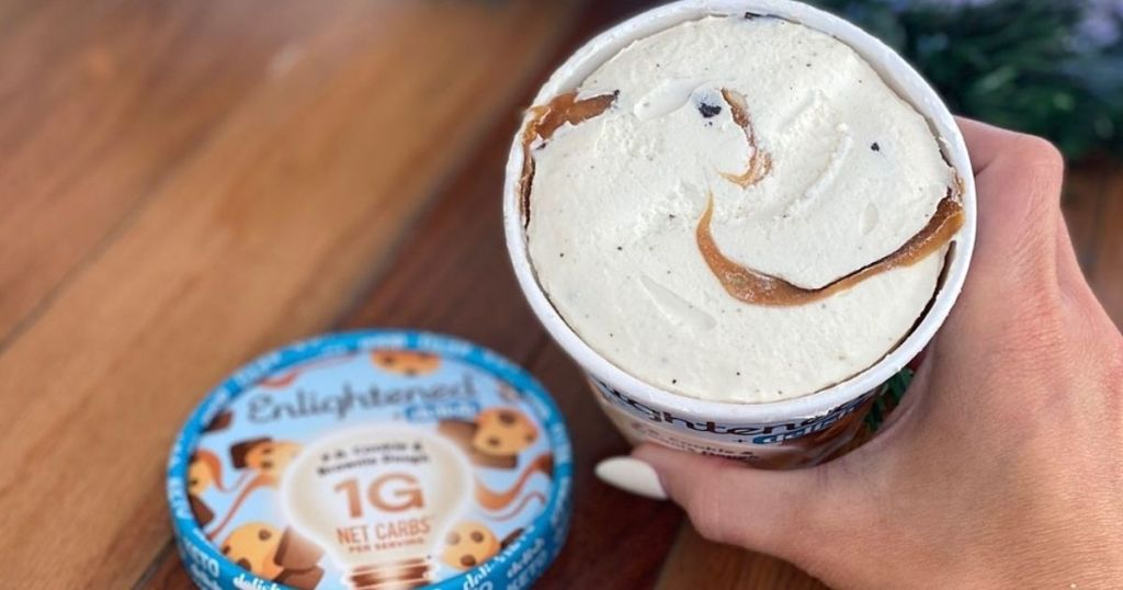 A hand holding a pint of ice cream with the lid off