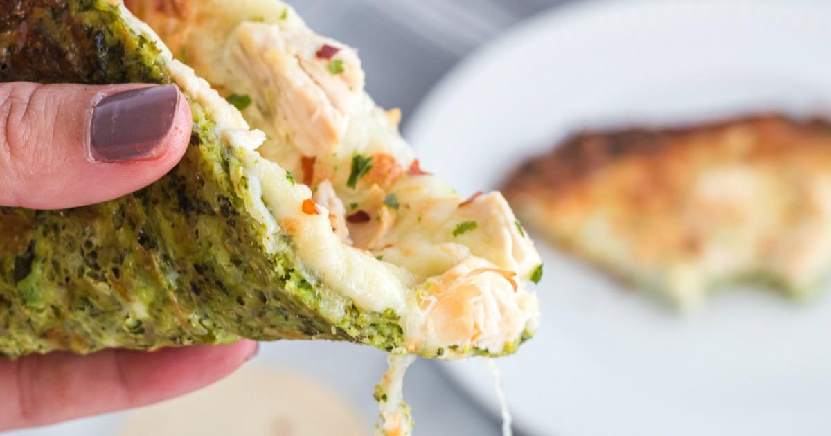 holding a slice of keto broccoli pizza