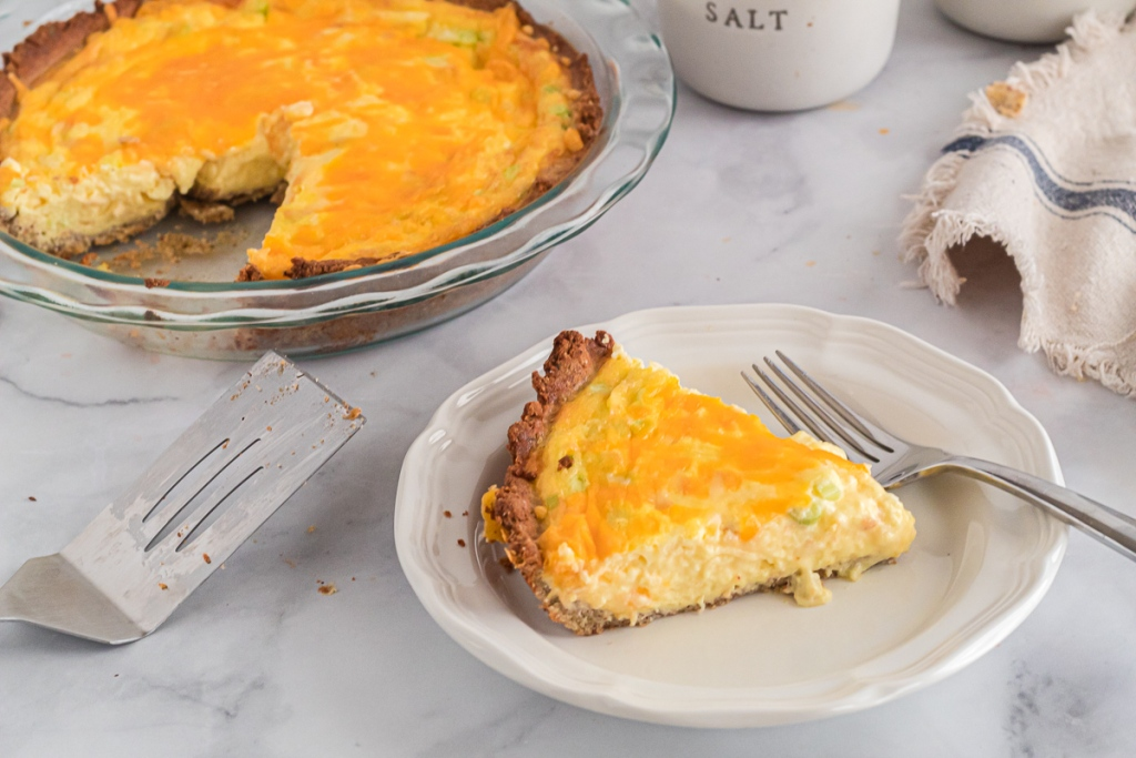 3 cheese quiche with a slice on a plate