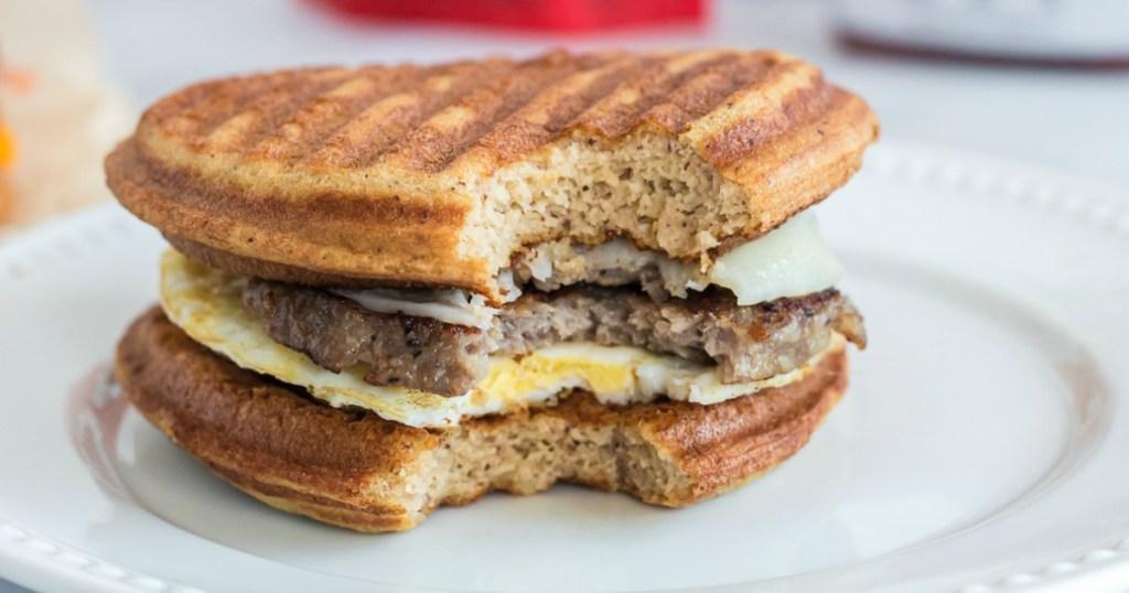 Bite taken out of Keto McGriddle Breakfast Sandwich on plate