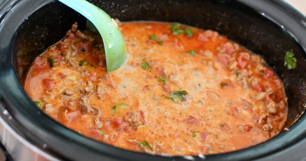 stirring a slow cooker with keto taco soup