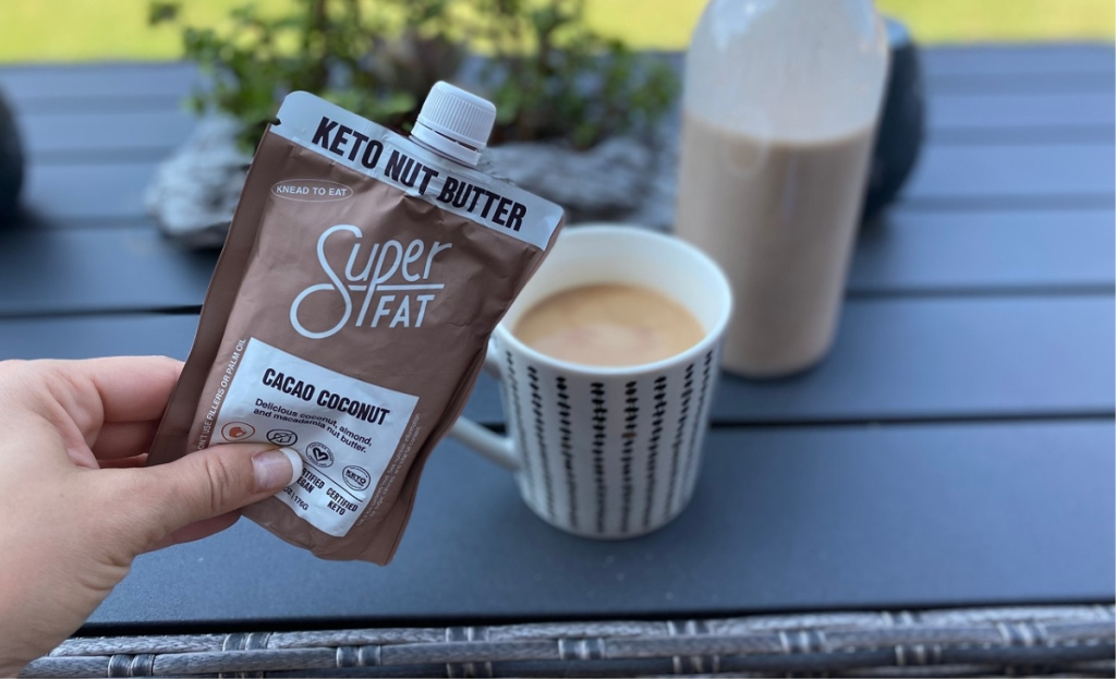 A hand holding a nut butter pouch in front of some coffee