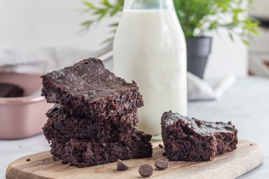stacked brownies with a glass of almond milk