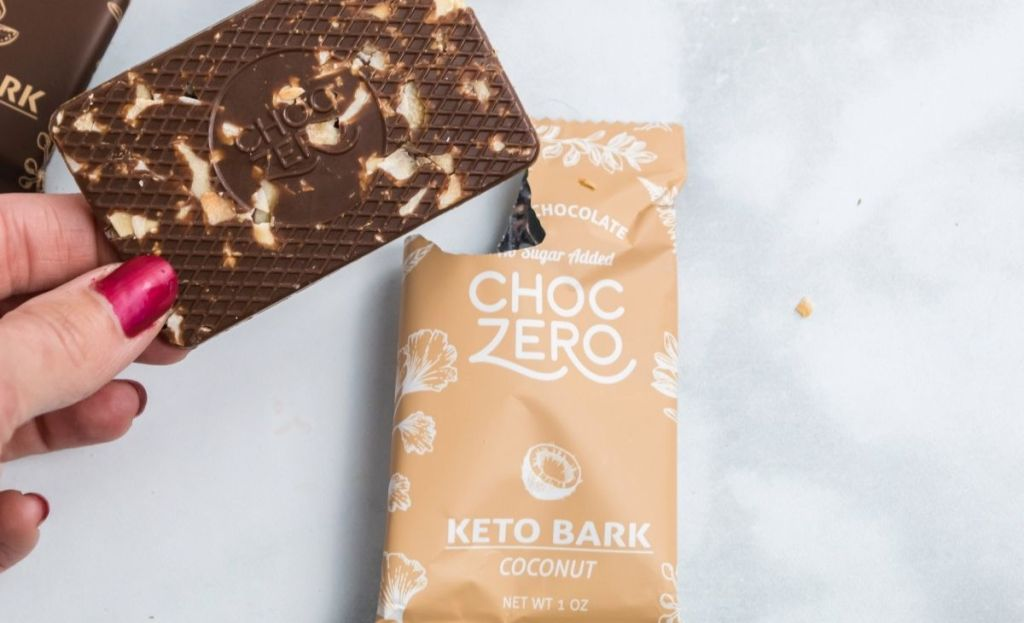 A hand holding a piece of keto bark next to the wrapper
