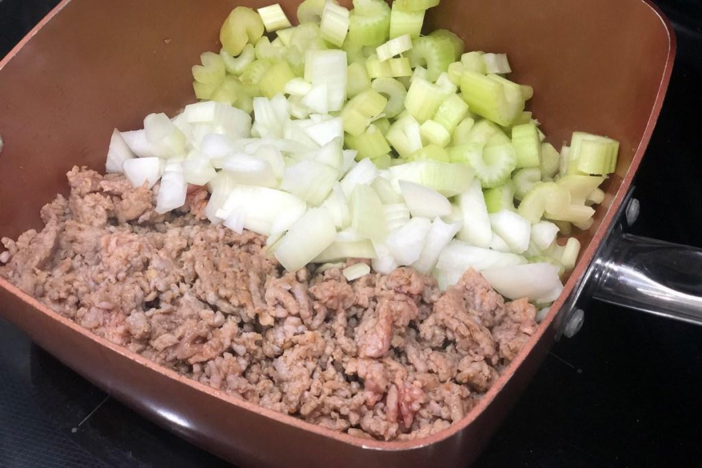 Sauté pan with ground sausage, onion, and celery
