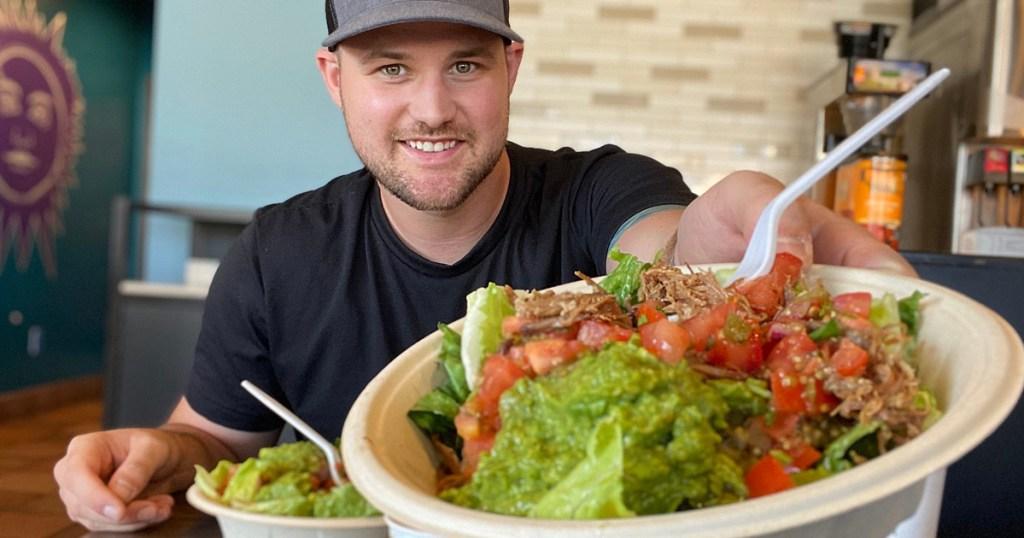 man holding qdoba salad bowl