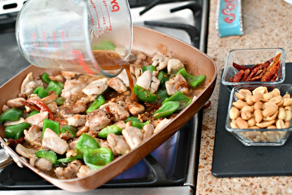 pouring kung pao sauce onto chicken