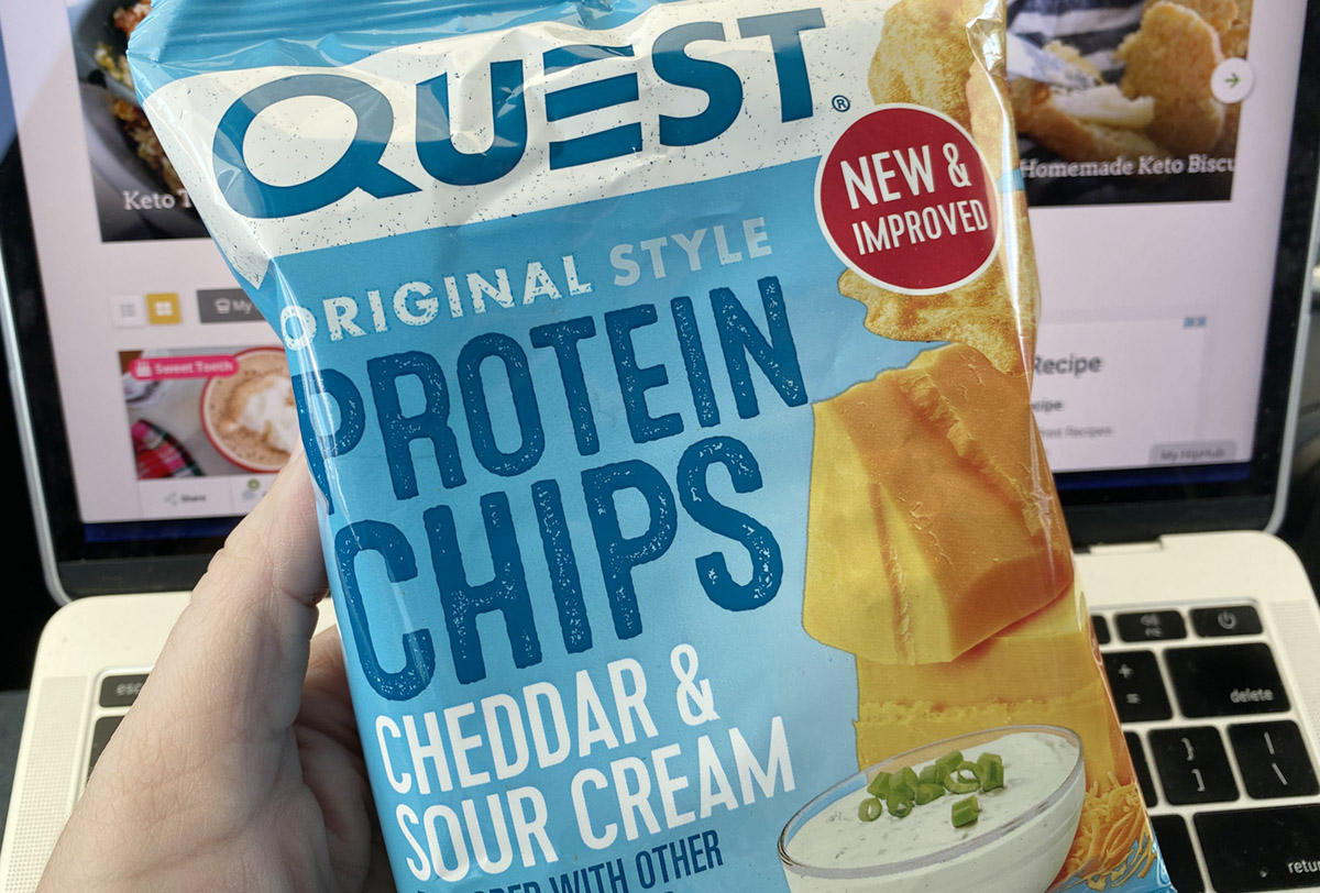 holding Quest Protein Chips Cheddar Sour Cream bag on front of macbook