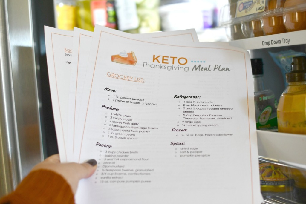 holding keto thanksgiving meal plan in front of fridge