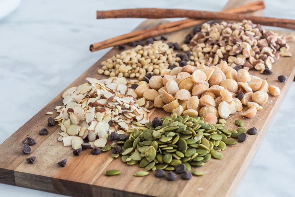cutting board of mixed nuts, chocolate chips and cinnamon sticks