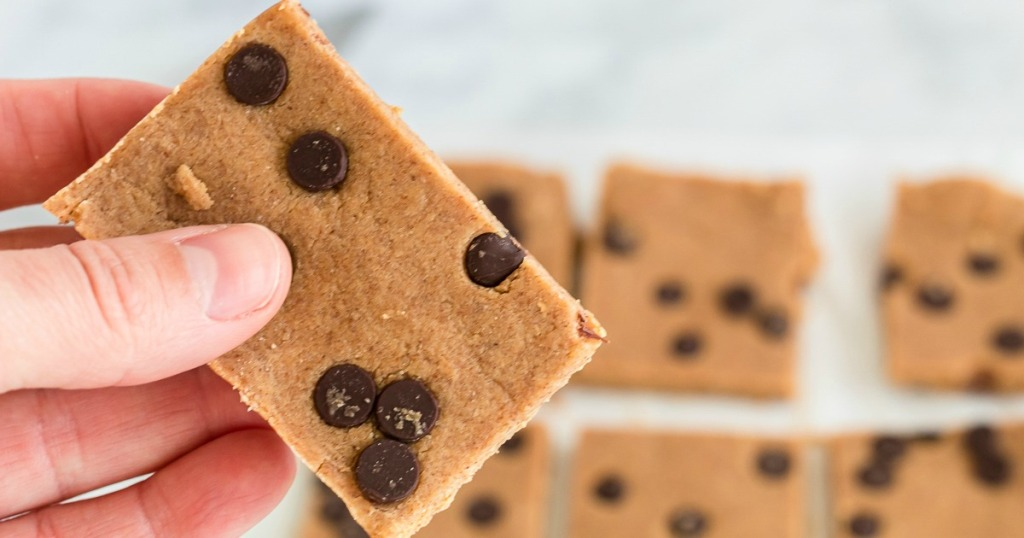 holding a cookie dough bar