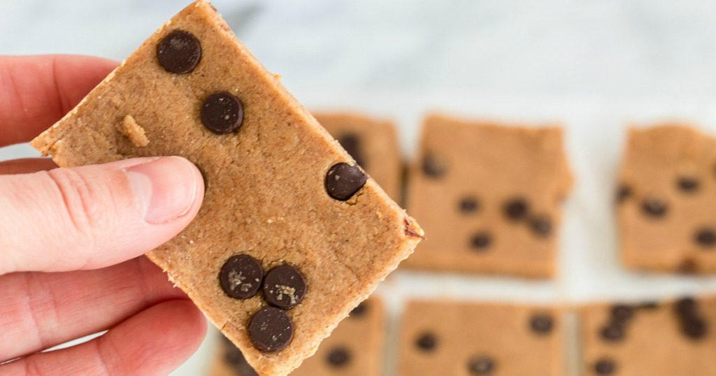 holding a cookie dough bar