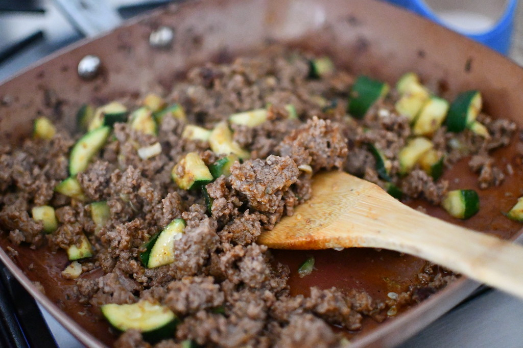ground beef taco meat in pan with zucchini