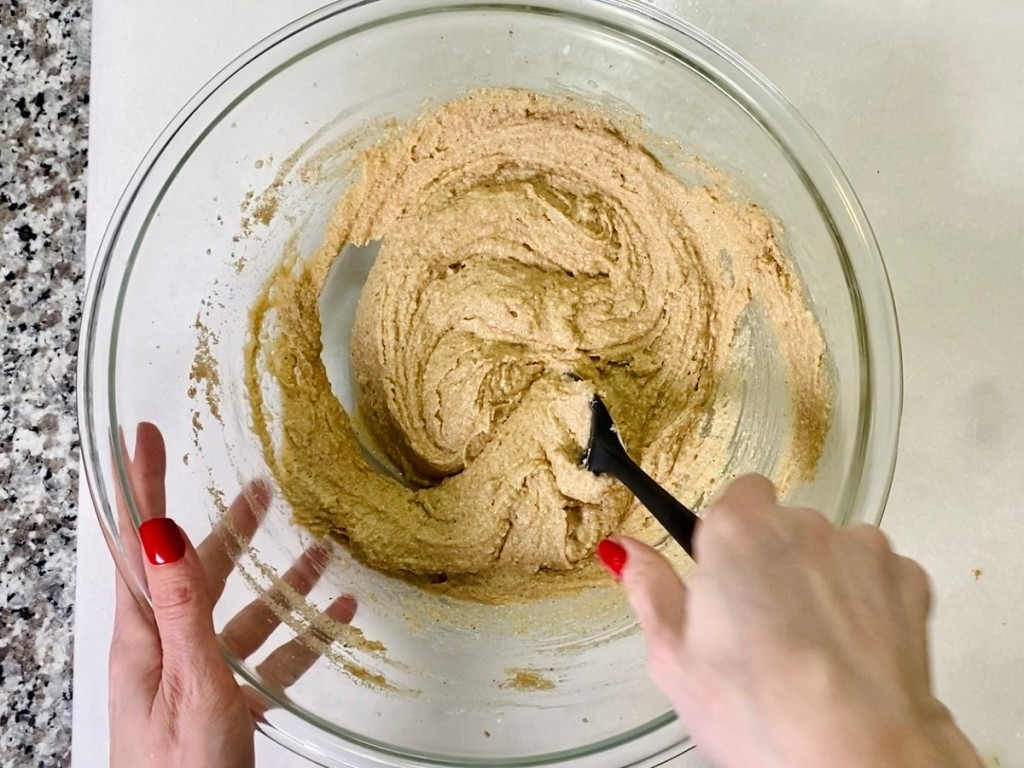 cake batter being hand mixed in glass bowl