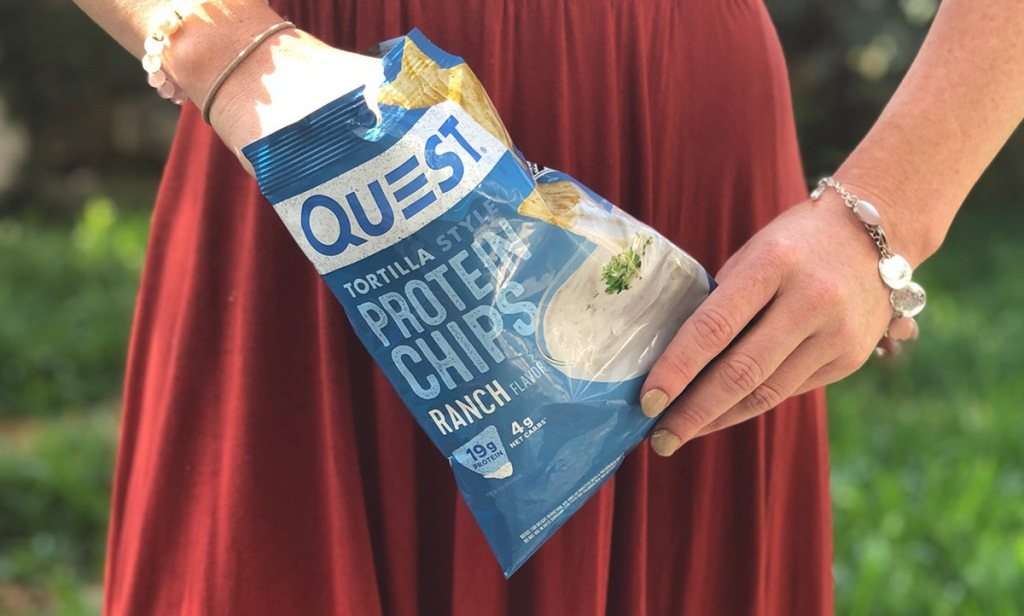 woman holding a bag of quest ranch protein chips