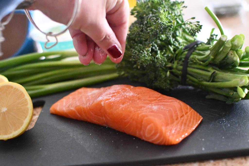 salting salmon on black cutting board with broccoli