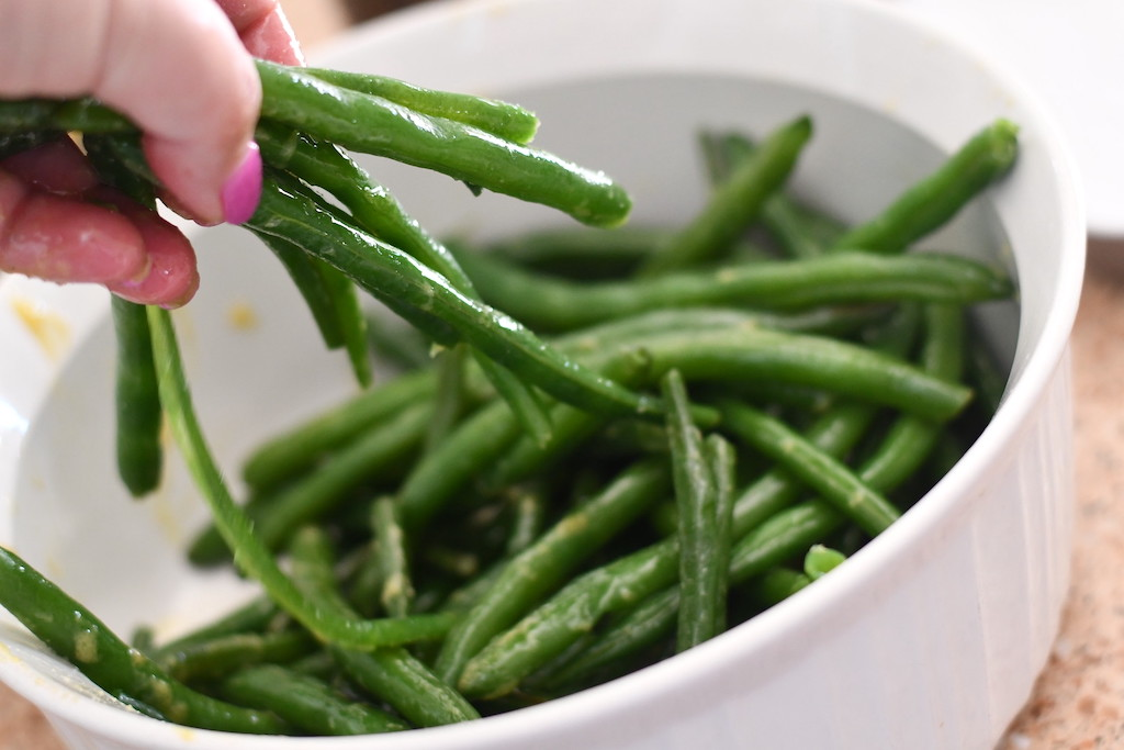 tossing green beans with sauce
