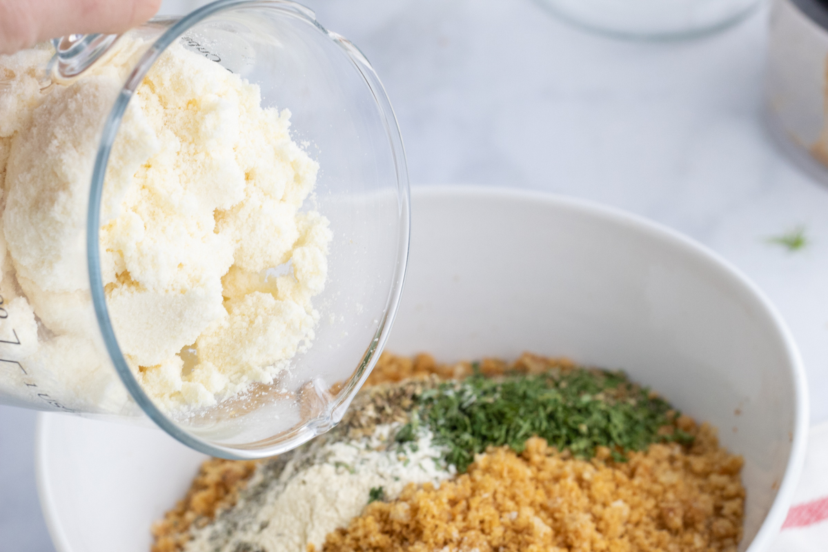 pouring parmesan cheese into bread crumbs seasoning blend