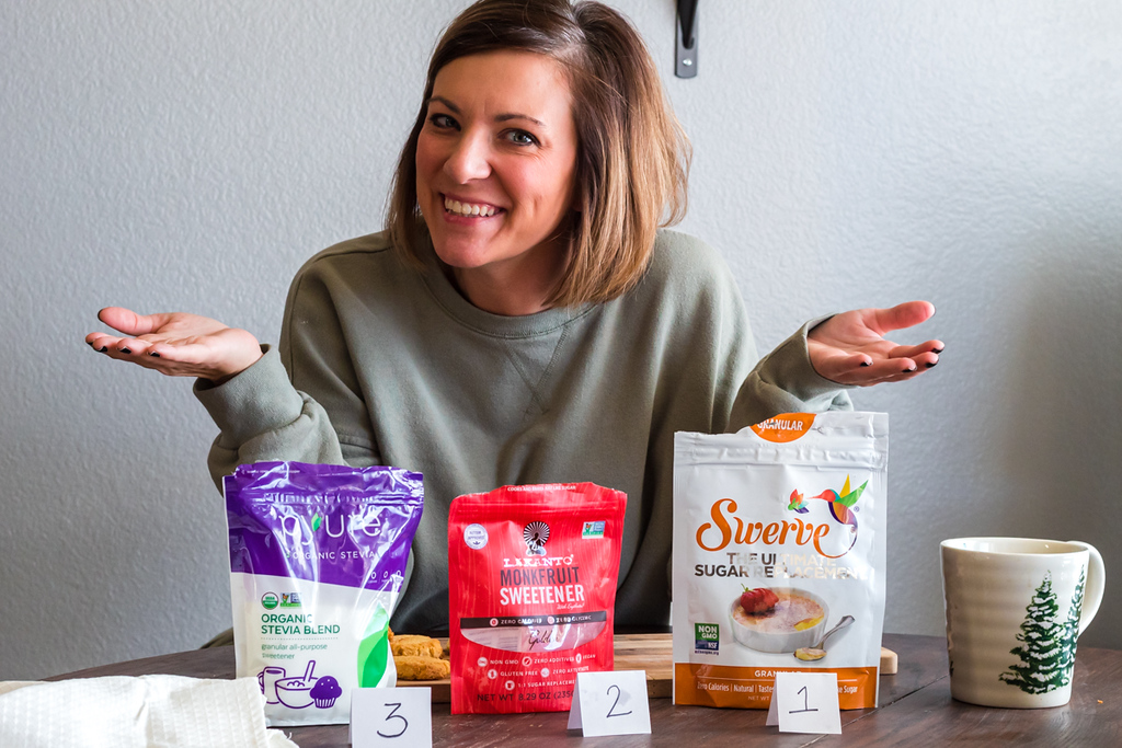 woman sitting behind three bags of alternative sweeteners