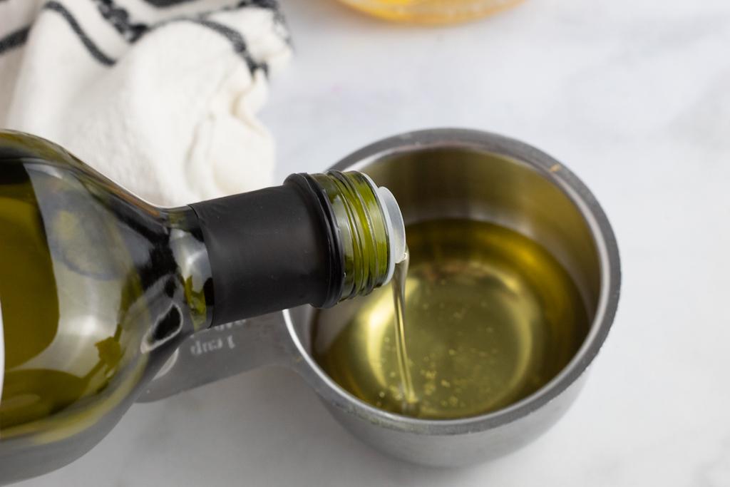 pouring avocado oil into measuring cup