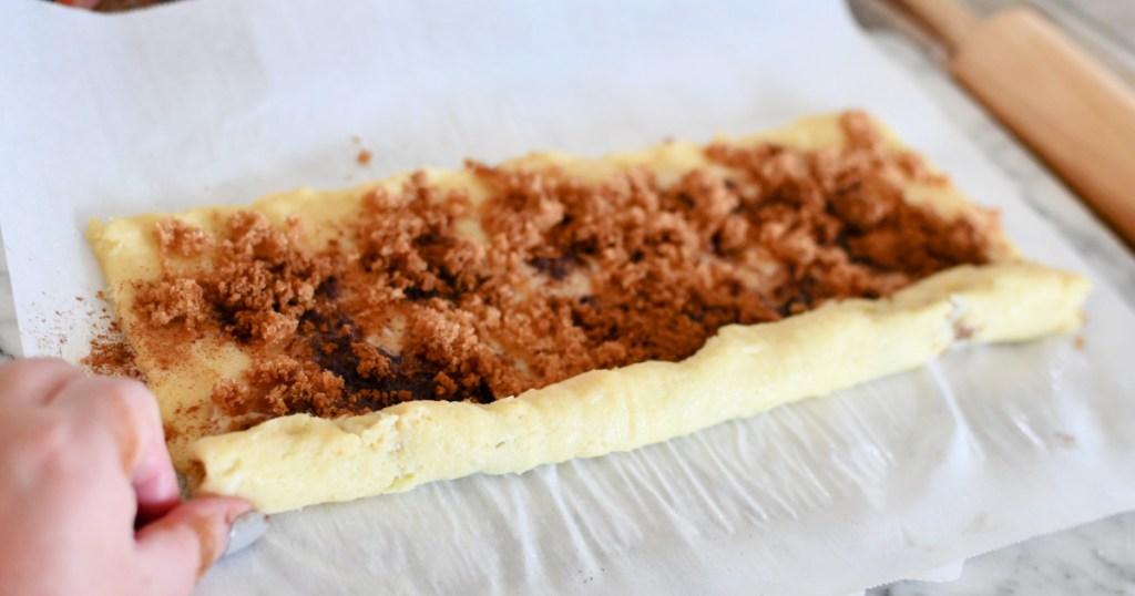 rolling up keto cinnamon roll