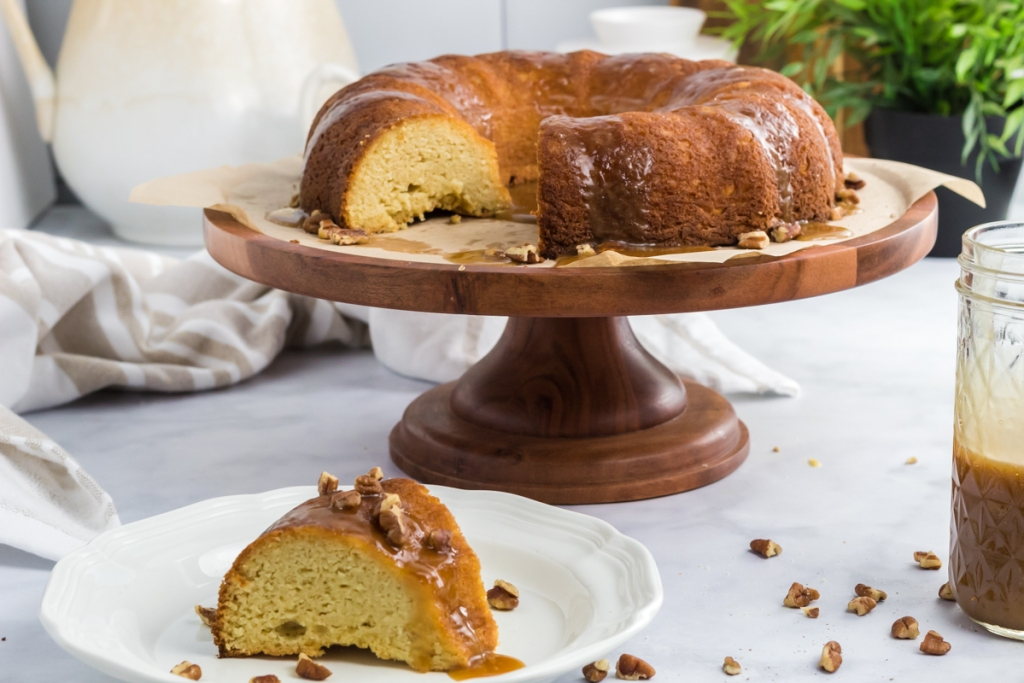 caramel bundt cake on cake stand and slice on plate