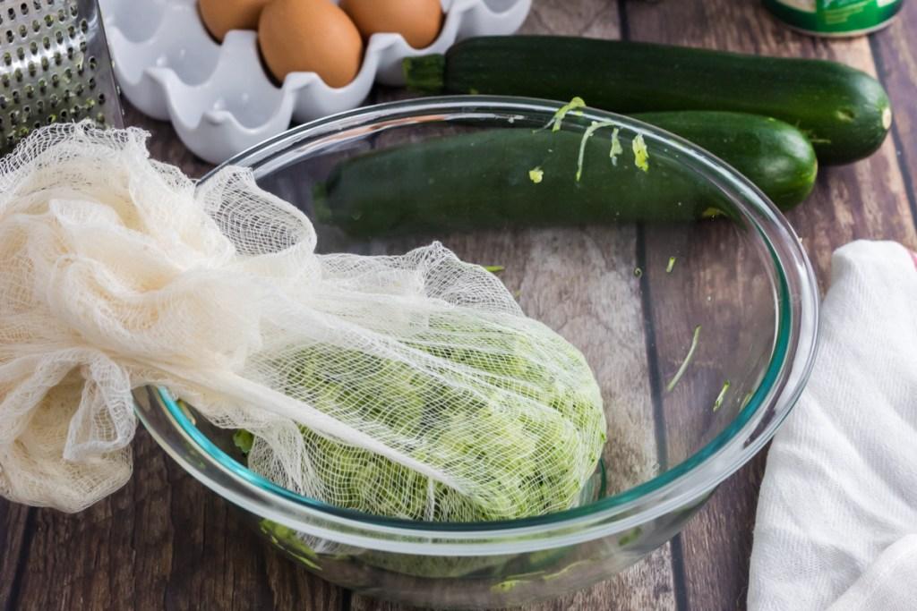 grated zucchini in a cheese cloth to drain liquid